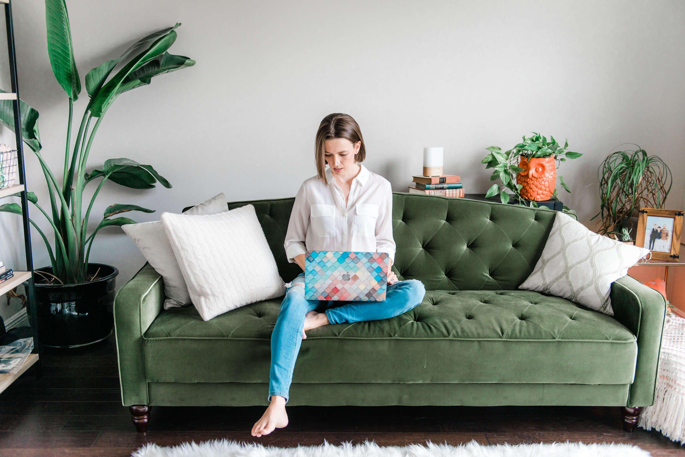 Tara sitting on green pin-tucked couch on laptop