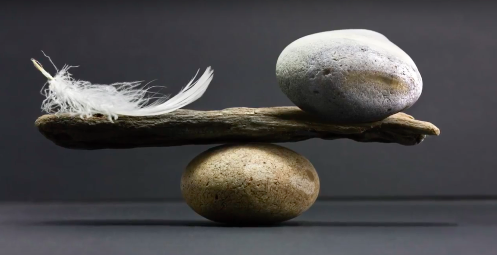 rock and feather being balanced on a stick and a rock