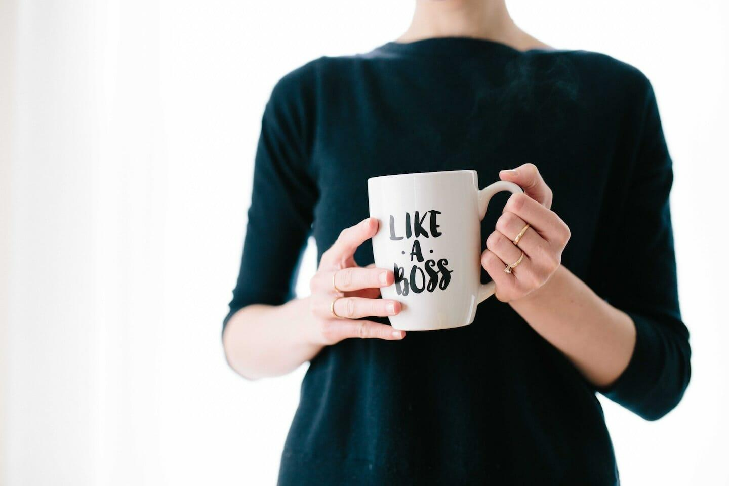 "Woman in black 3/4 sleeve shirt holding a white mug that says ""LIKE A BOSS""."