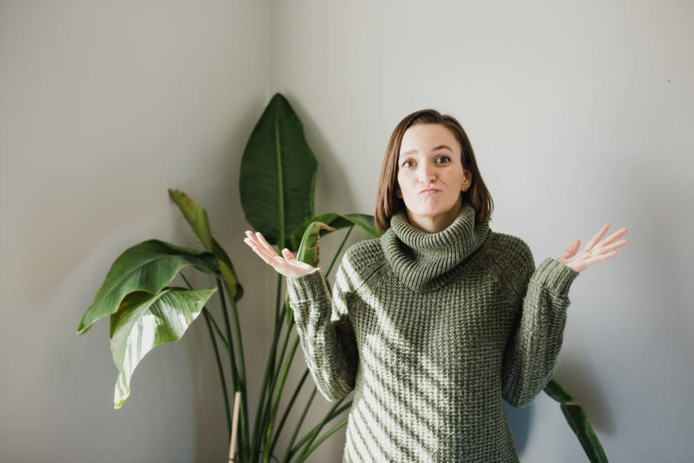 Tara wearing green sweater with hands up in uncertainty