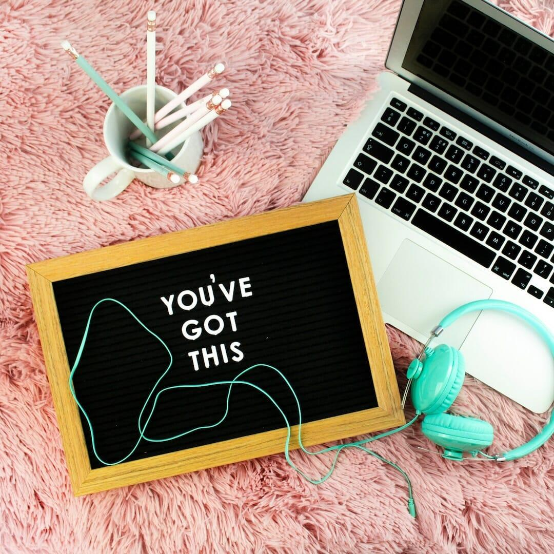 """Letterboard that says you've got this"""" on pink carpet beside blue headphones"""