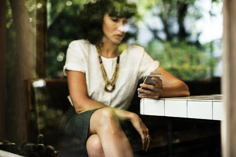 woman looking on her phone pictured through window