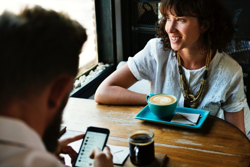 Man and woman with coffee at table, as woman smiles out the window