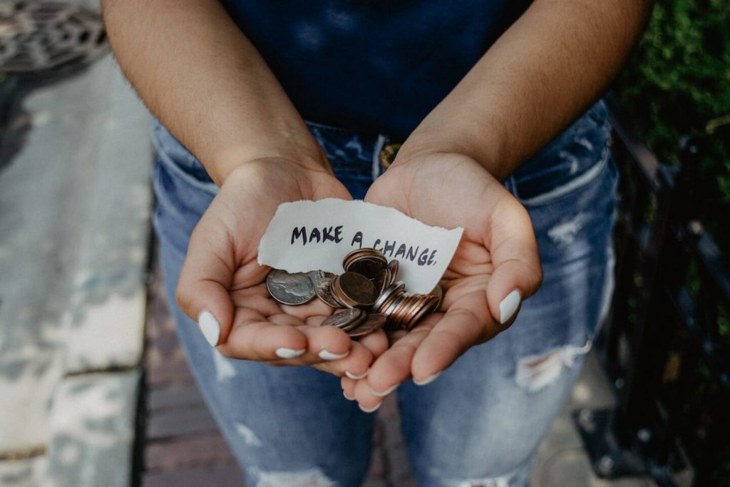 """hands full of change with a piece of paper that says """"make a change"""""""
