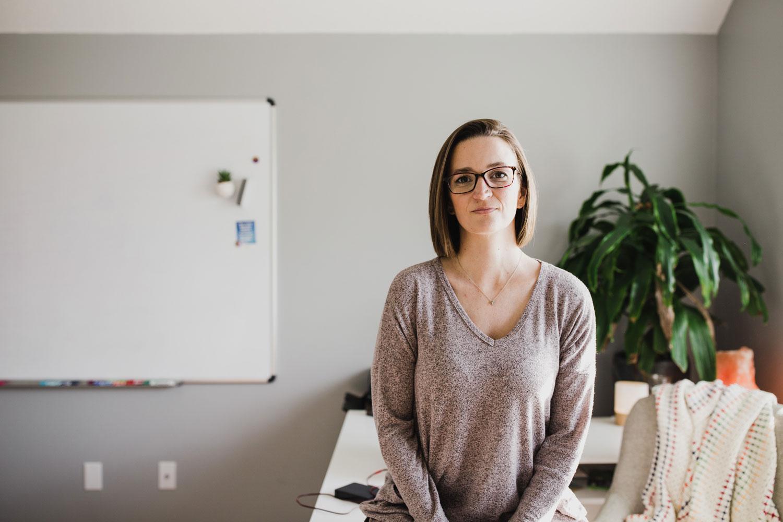 Tara in long sleeve gray tri-blend long sleeve shirt sitting on her desk in her office