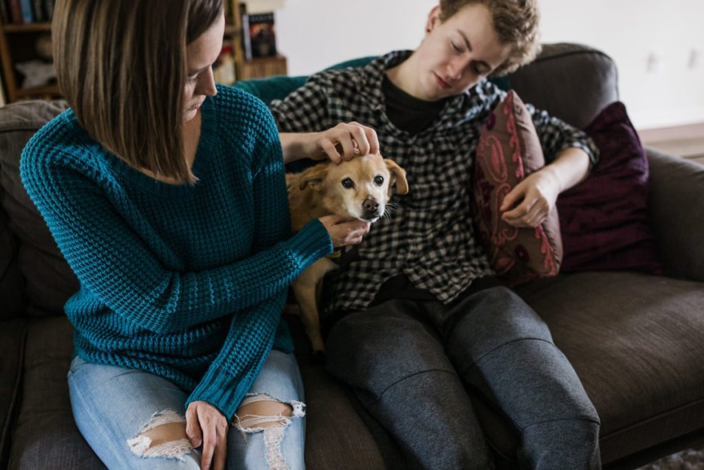 Tara and Zeb petting their dog together on the couch