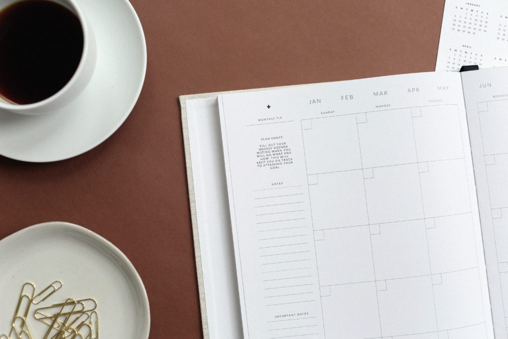 Monthly calendar with coffee and paper clips beside it