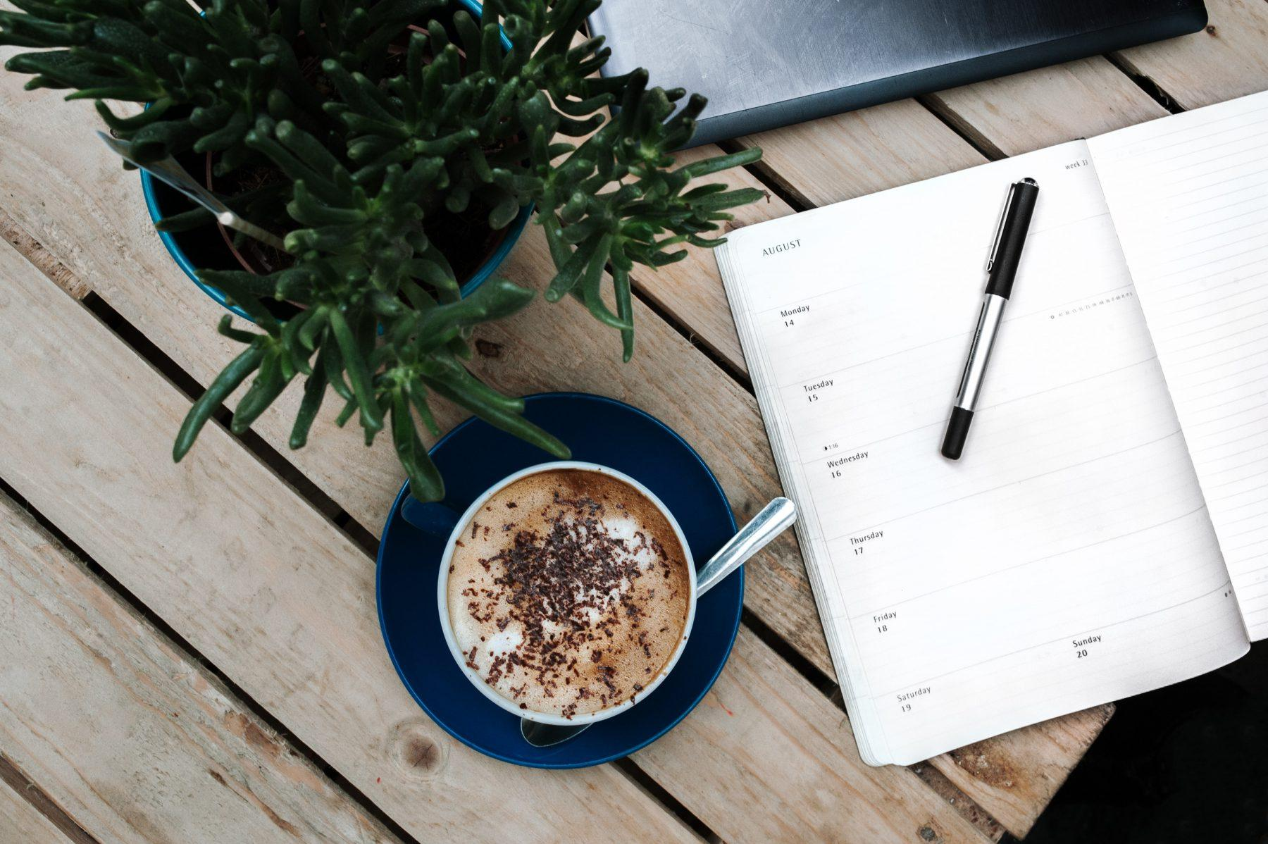 top view of a coffee, notebook and paper and plant