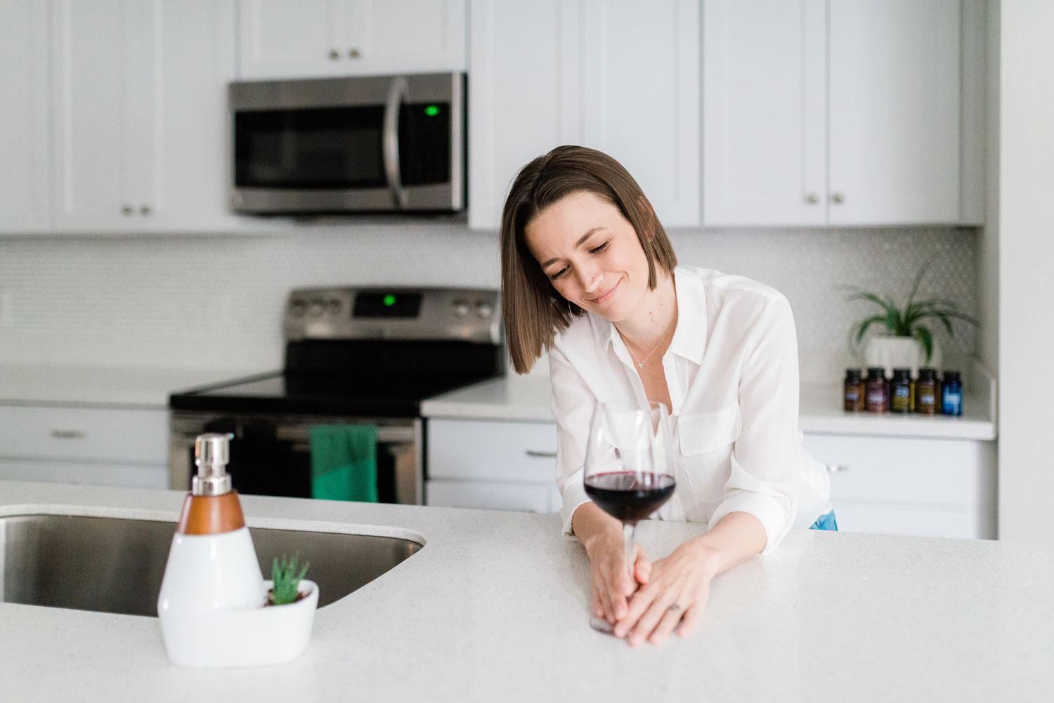 Tara smiling with a glass of wine in her kitchen