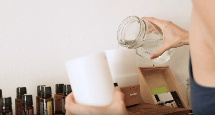 Tara filling up a diffuser with water beside multiple bottles of essential oil