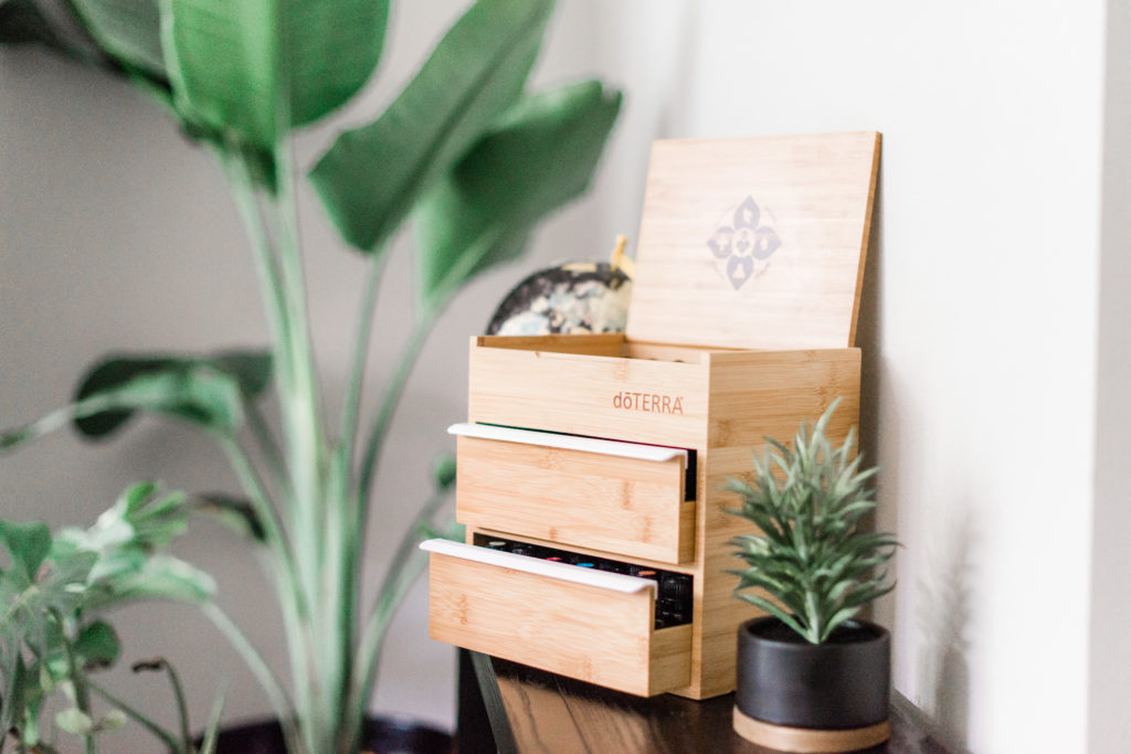 Wooden doTERRA box of oils with foliage in the foreground and background