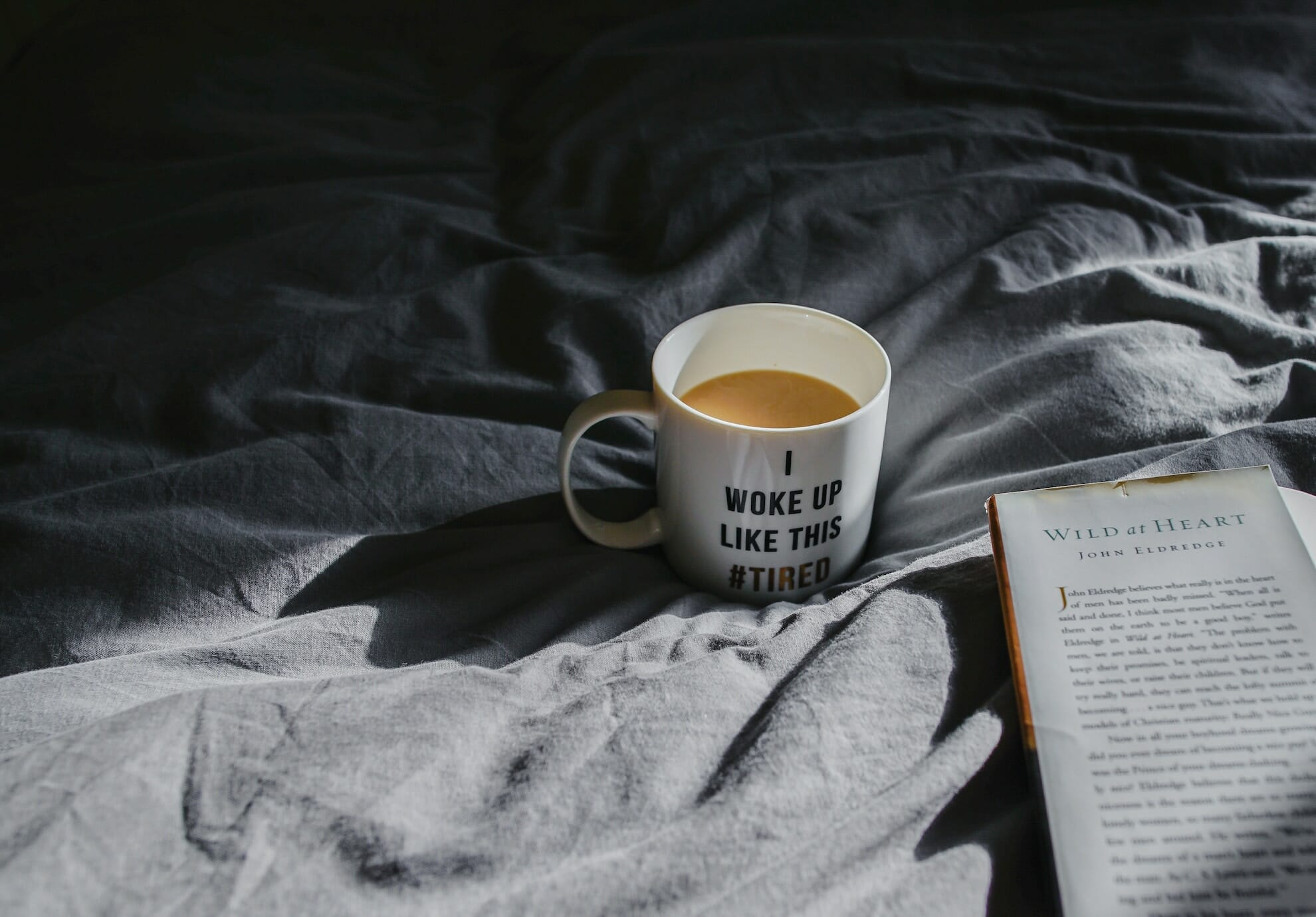 "Coffee cup on bed with quote ""i woke up like this #tired"""