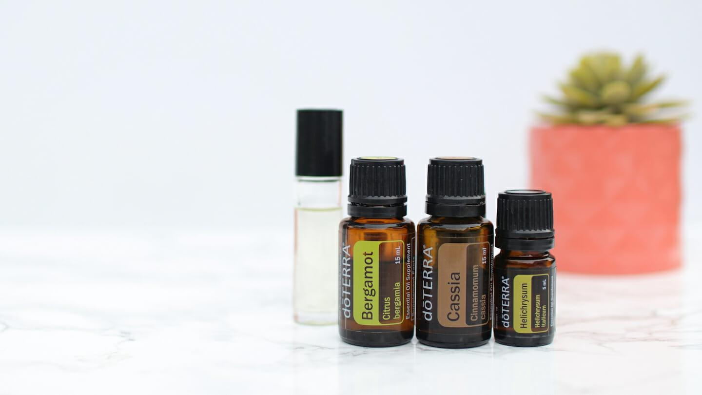 Bergamot, Cassia, and Helichrysum essential oils with carrier oil rollerball on white background and tabletop