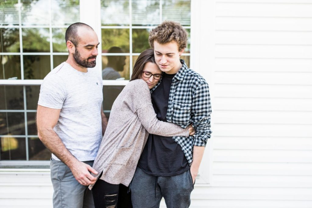 Justin, Tara and Zeb outside of their Florida home, Tara hugging Zeb before he leaves