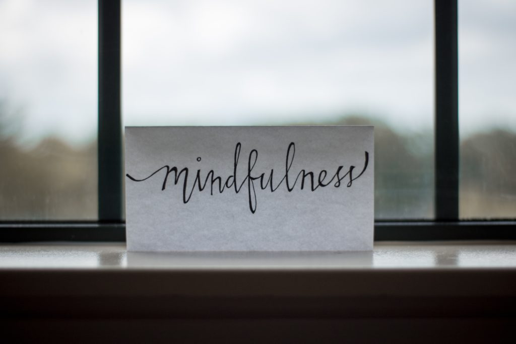 "the word ""mindfulness"" on a piece of paper in the window"