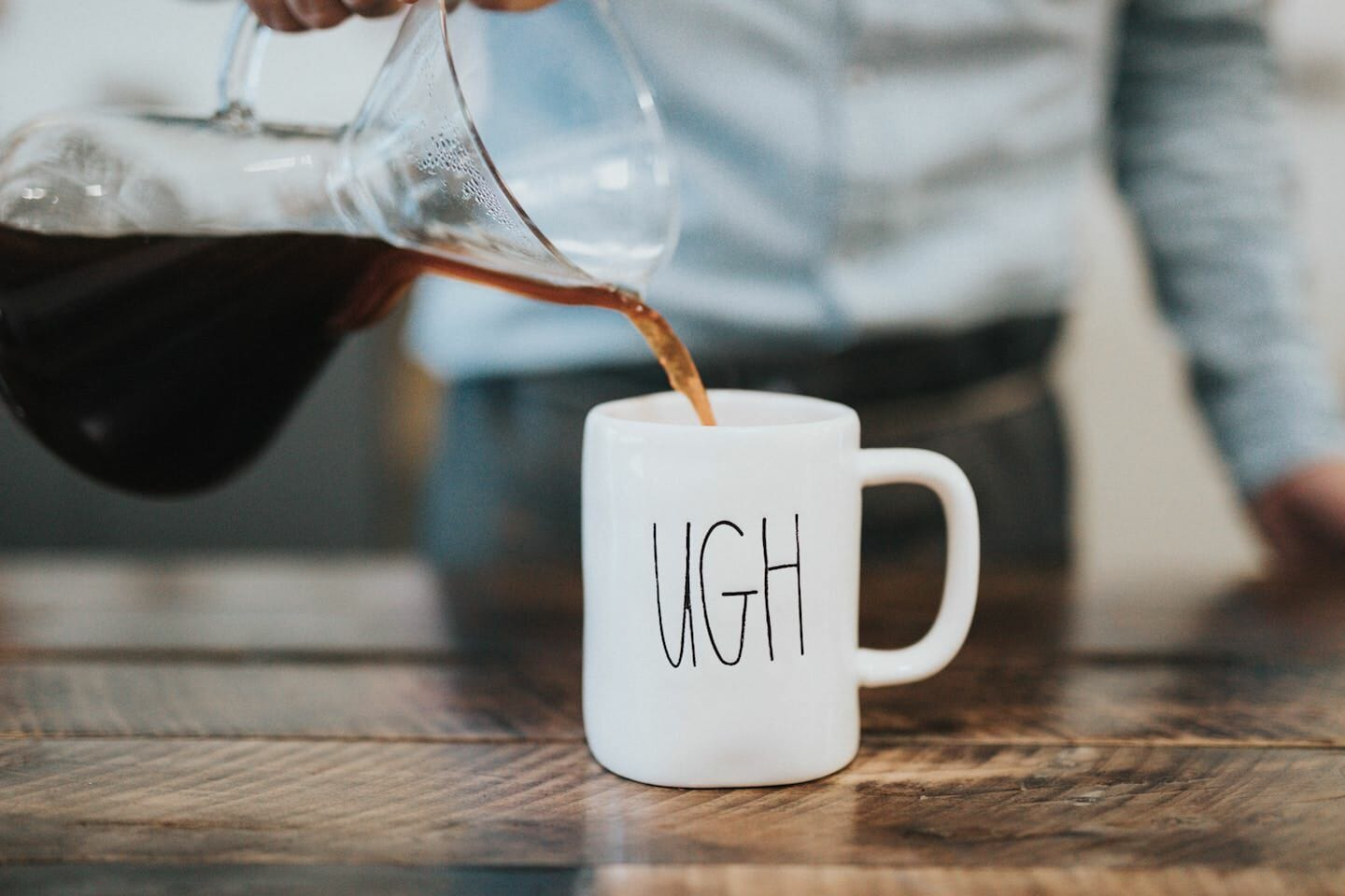 """Pouring coffee into a mugh that says """"ugh"""""""