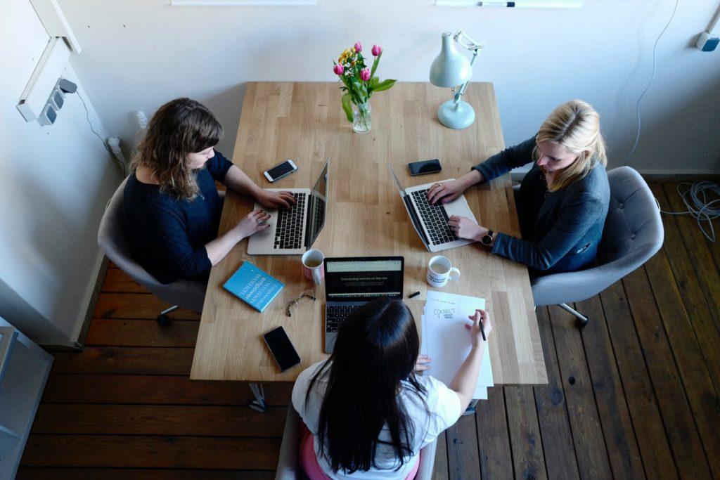 3 women sitting around a table working