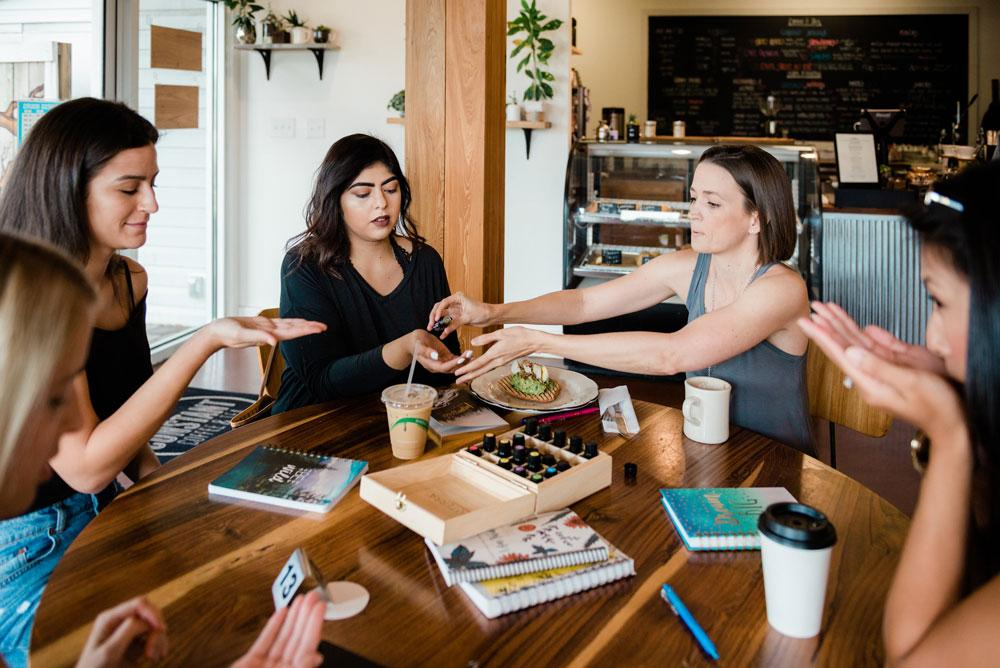 women sitting with Tara in coffee shop sharing oils