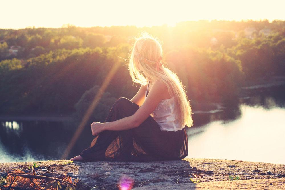 girl lit my the sun looking over view of lake and woods