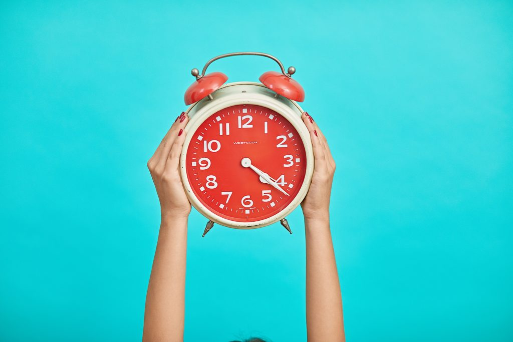 Hands holding up a red alarm clock wit aqua background