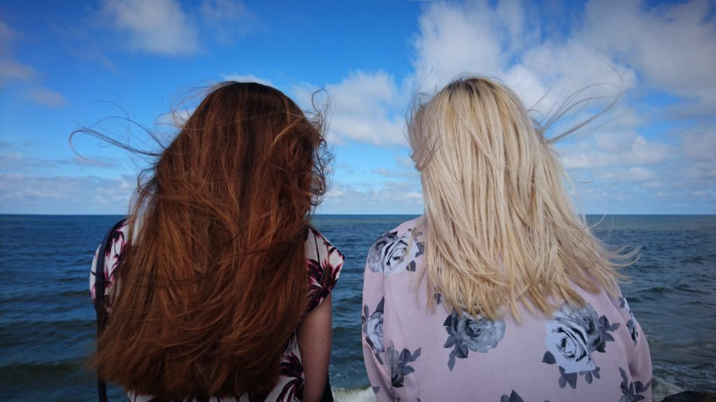 2 girls, one brunette and one blonde, looking over the ocean side by side.