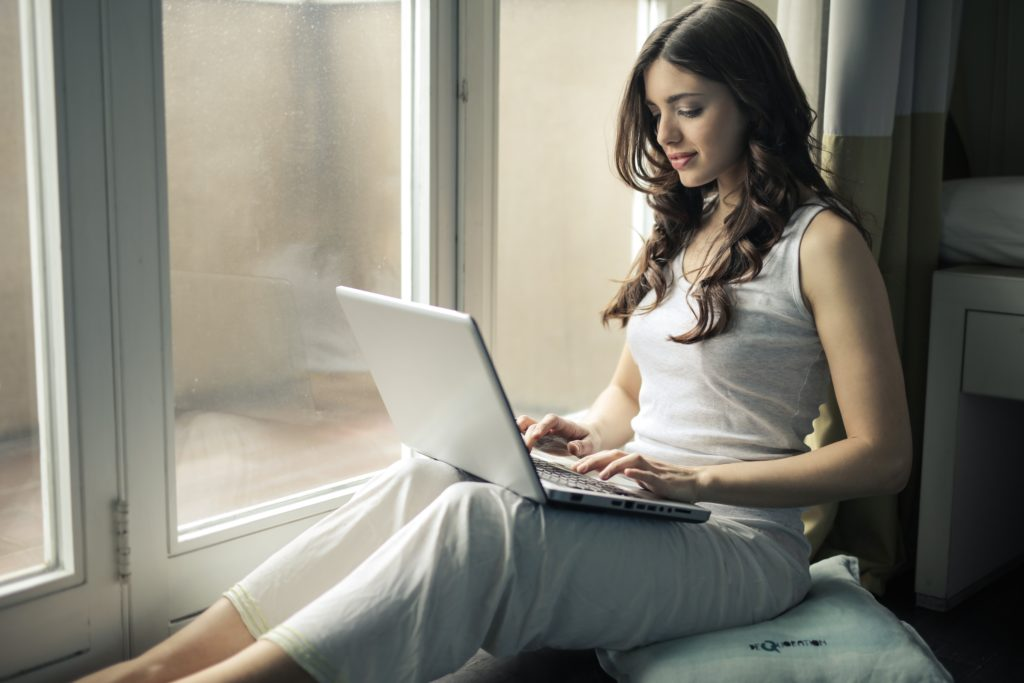 woman on computer in window sill