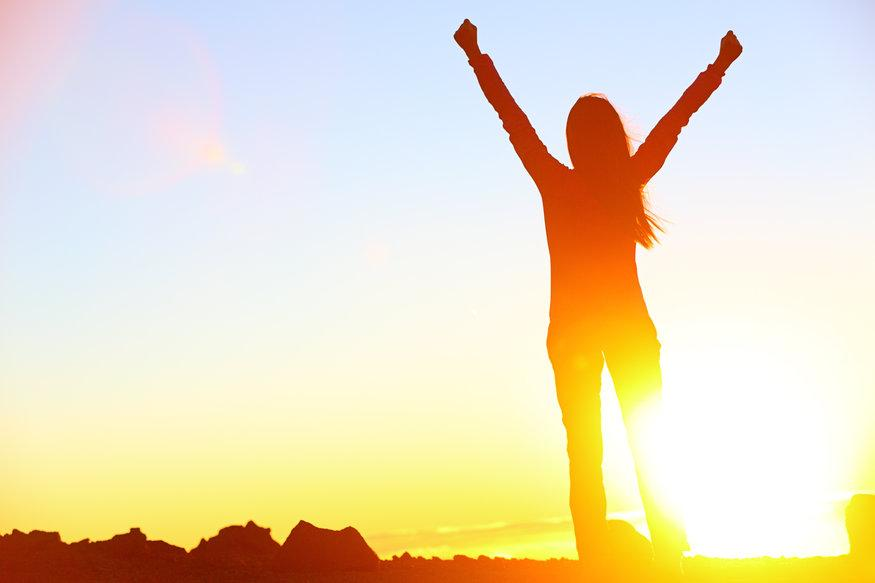 woman with celebratory arms up silhouetted by the sun