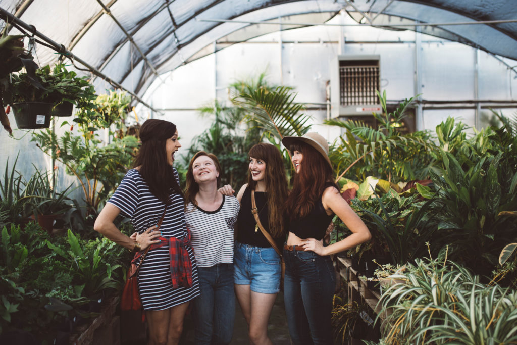 women hanging out in greenhouse