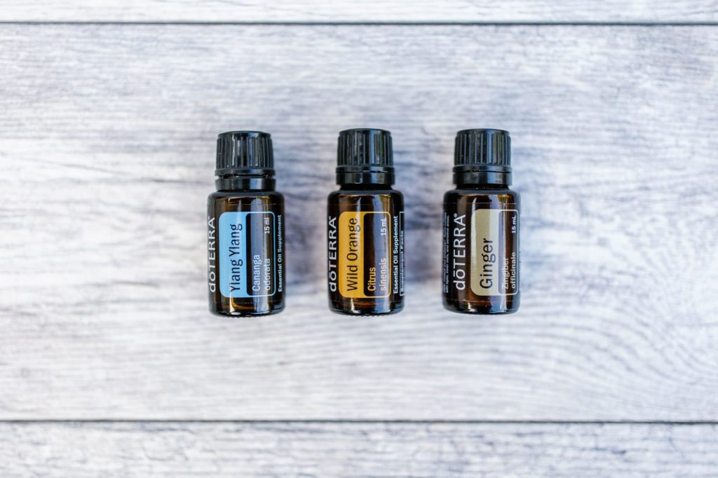 Ylan Ylang, Wild Orange, and Ginger essential oils laid flat beside each other on wood table