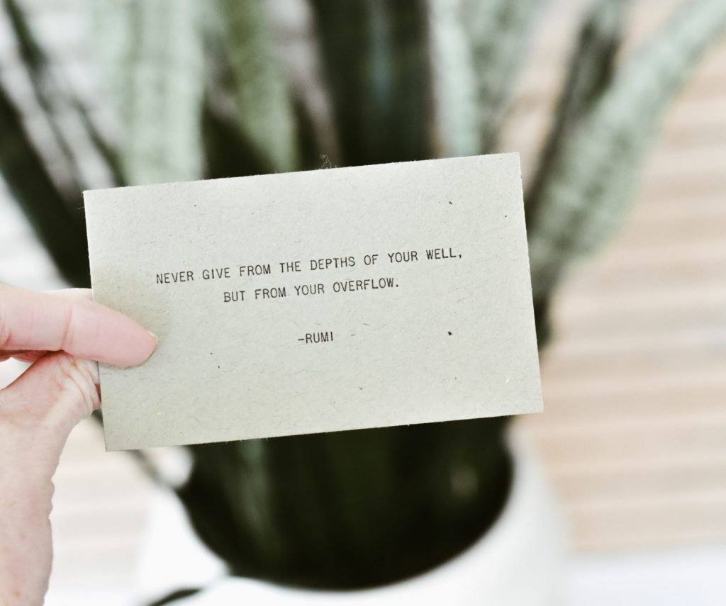 "A hand holding a piece of paper that says""Never give from the depths of your well. But from your overflow."""