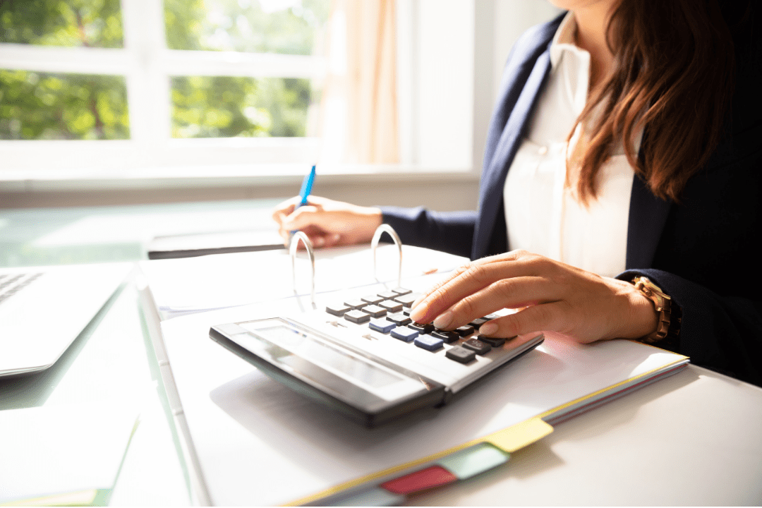 Business woman using a calculator and writing