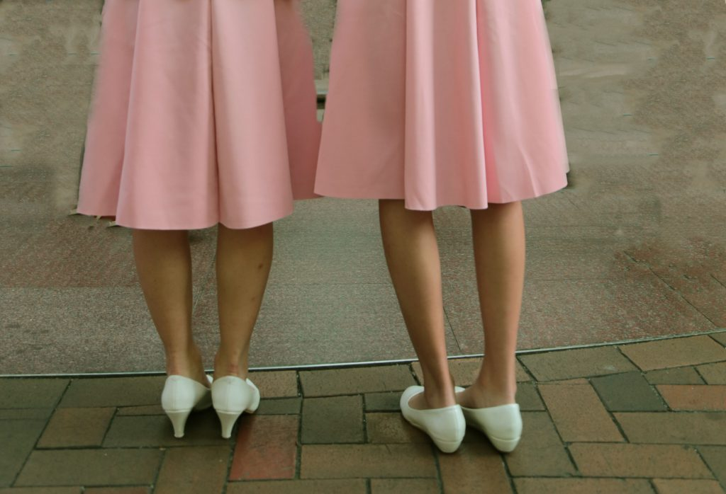 Image of two woman wearing almost identical pink skirts and white shoes
