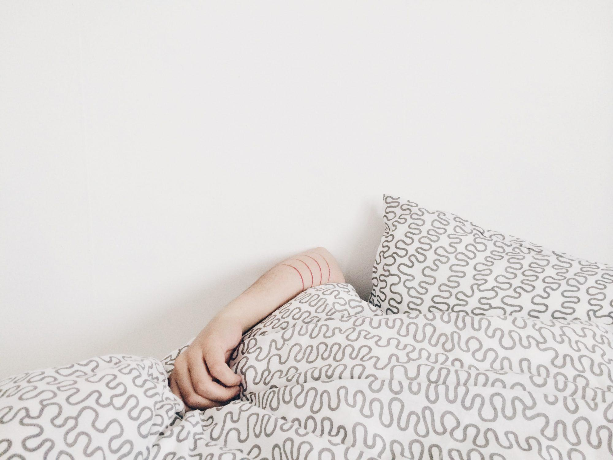 Woman laying in bed covering her face with white printed comforter