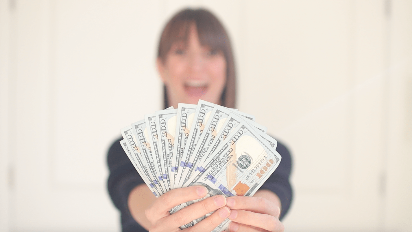 Tara out of focus holding money in focus