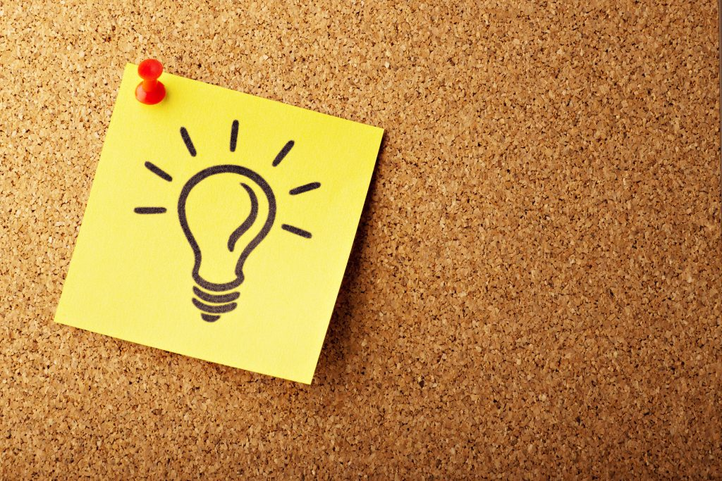 Post-it note with lightbulb pinned to corkboard