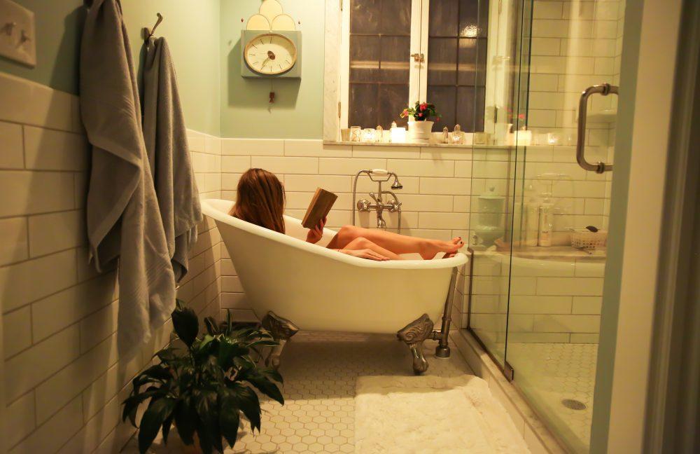 Woman in white ceramic bathtub reading.