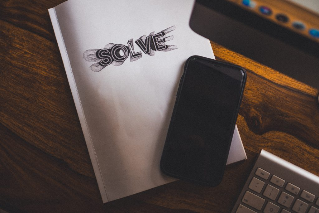 "Black phone on top of white notebook that says ""solve""."