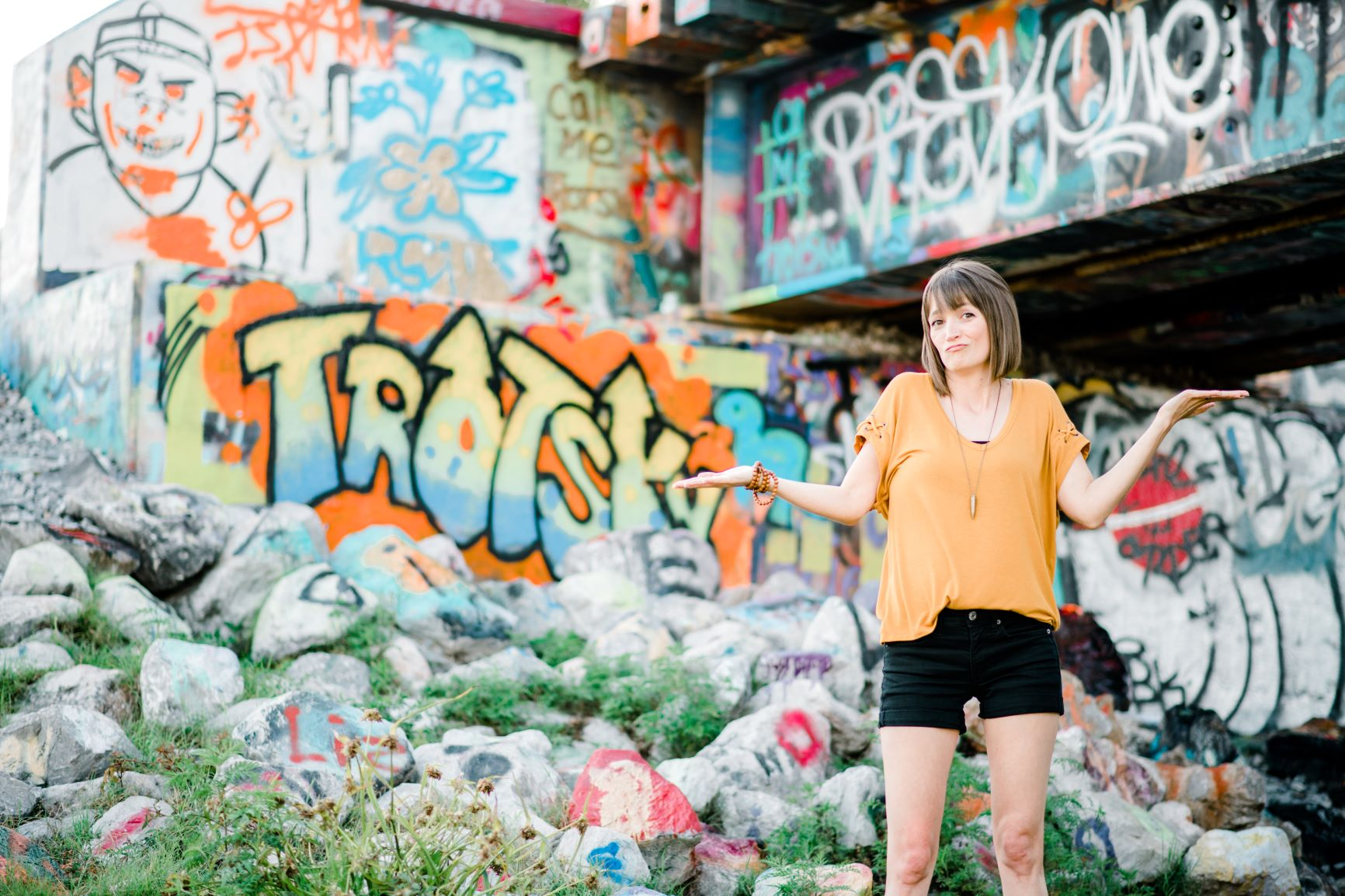 Tara in a yellow shirt and black shorts with arms out looking unsure, with a graffiti background.