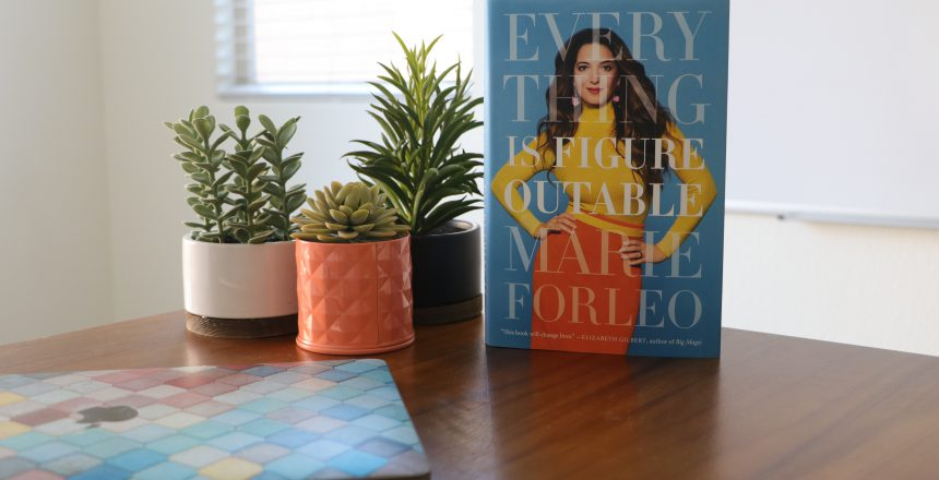 Marie Forelo's book Everything is Figureoutable sitting on desk beside plants and laptop