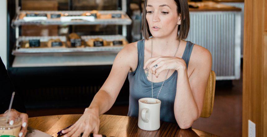 Tarain gray tank top explaining doTERRA oils in coffee shop