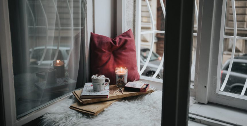 A comfy spot next to window sill with pillow, candle, a pad of paper and a mug.