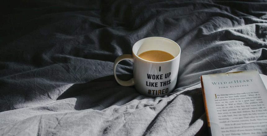 Coffee cup on bed with quote
