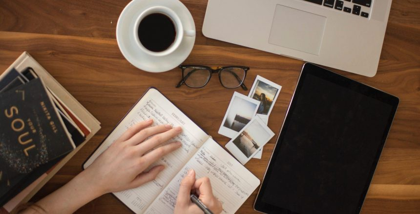 girl writing in journal in workspace