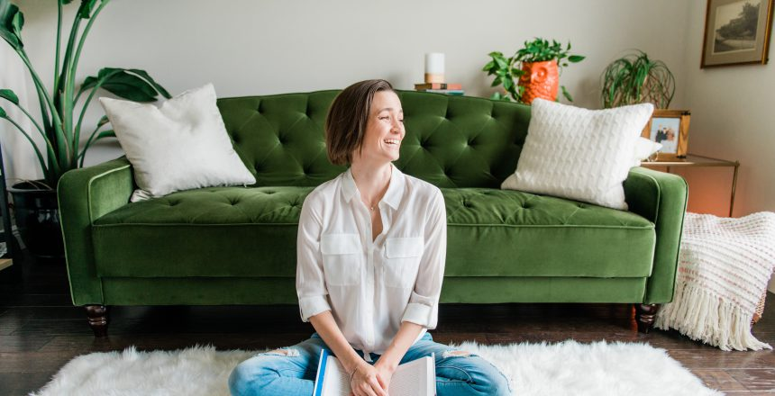 Tara sitting on the ground laughing with book in hand, emerald couch in the background