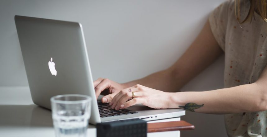 Woman working on silver Apple laptop